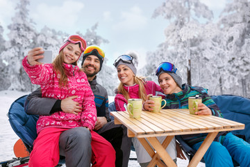 young girl with family enjoying in winter vacation on snow and making selfie