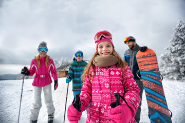 smiling girl with family on ski slope on vacation in mountain