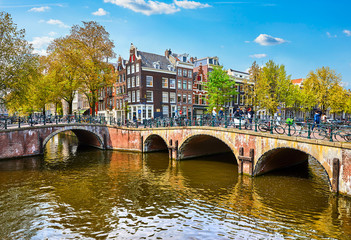 Fototapete - Bridge over channel in Amsterdam Netherlands houses river Amstel