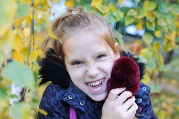 Young girl hugs a teddy hare and smiles. She has a funny face
