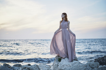 Caucasian woman wearing dress on rocks near ocean