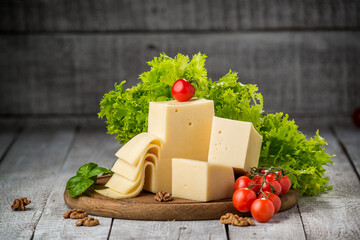 Cheese and vegetables on a wooden table,