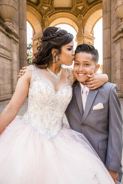 Hispanic girl wearing gown kissing boy on forehead