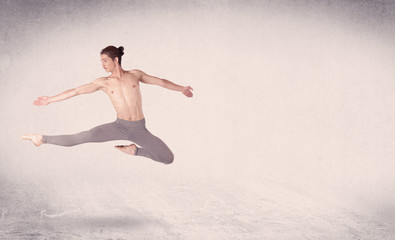 Modern ballet dancer performing art jump with empty background