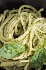 Spaghetti pasta with sauce pesto in black bowl, closeup background.