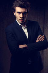 Charismatic business handsome male with folded arms in blue fashion suit and white style shirt looking on dark shadow background.
