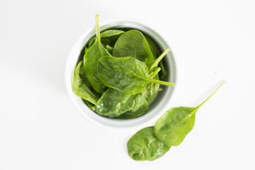 Fresh wet green baby spinach leaves in a bowl, closeup on white background.