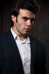 Handsome success brunette young man looking serious in fashion suit with white shirt. Closeup portrait on dark background in dramatic light