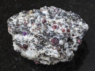 rough corundum crystals in gneiss stone on dark