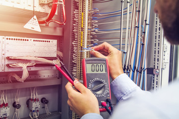 Engineer tests industrial electrical cabinet. Wire in hand of electrician with multimeter. Professional in control panel of industrial equipment.