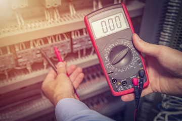 Service engineer with multimeter tester in hands close up. Electrical measurements in electric cabinet. Support specialist with test device