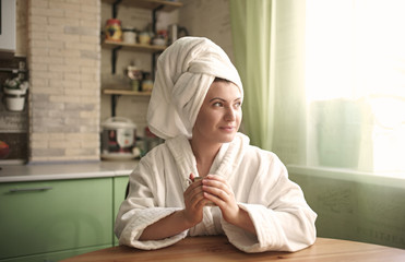 Woman in bathrobe and towel warming hands on cup