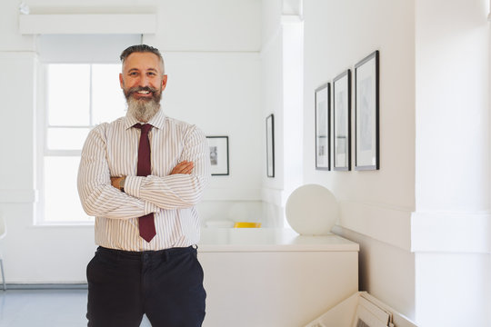 Portrait of smiling Caucasian businessman with arms crossed