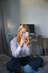 A young woman playing with a smart phone on a bed