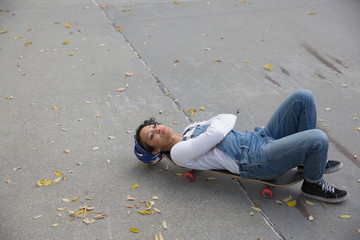 A young woman lying down on a skateboard