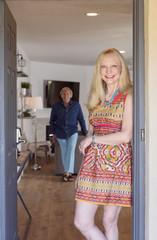 Man watching Caucasian woman posing in doorway