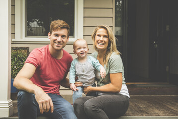 Portrait of Caucasian couple with baby son sitting on porch