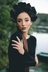 Middle Eastern woman wearing black dress in boat on lake