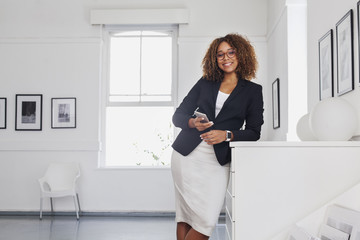 Mixed race woman texting on cell phone in gallery