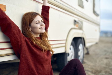 Caucasian woman stretching arms and leaning on motor home
