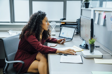 Mixed race businesswoman using computer in office