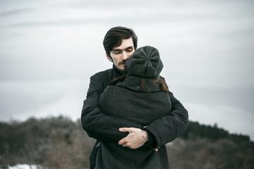 Caucasian couple hugging on hill