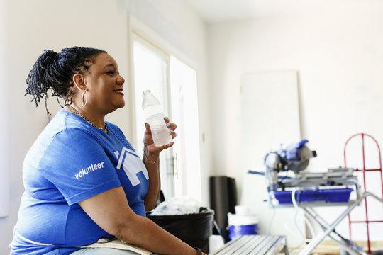 Black volunteer woman drinking water