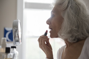 Older woman applying lipstick in mirror
