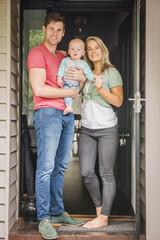 Portrait of Caucasian couple with baby son in doorway