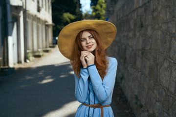 Pensive Caucasian woman wearing hat near stone wall