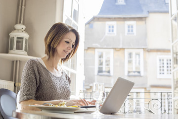 Caucasian woman typing on laptop and eating meal