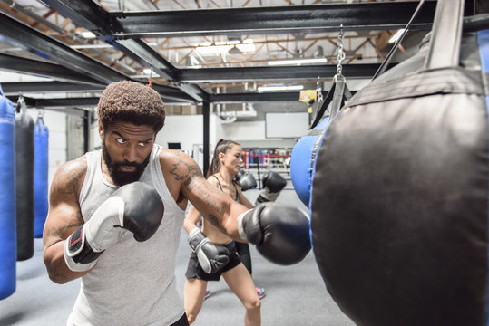 Man and women wearing boxing gloves hitting heavy bags