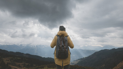 Young Caucasian female hiker in yellow raincoat wearing backpack enjoys the mountain view in French Alps