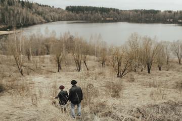 Middle Eastern couple walking on hill near lake