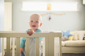Smiling Caucasian baby boy standing in playpen