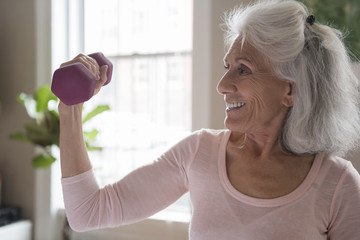 Smiling older woman lifting weights