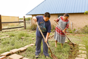 Mother and son shoveling in garden
