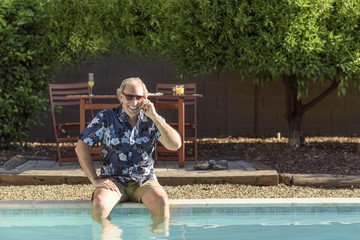 Caucasian man talking on cell phone with legs in swimming pool