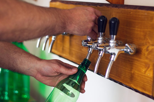 Man pouring wine into a plastic bottle