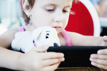 Social Media addiction. beautiful baby girl  holding phone (psychological problems, media mania, education)