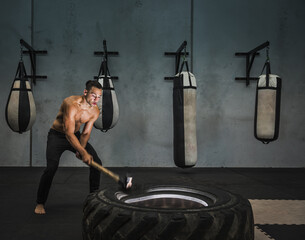 Hispanic man hitting tire with sledgehammer