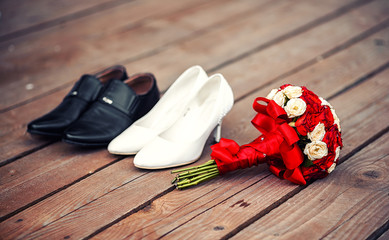Black male and female white shoes lying on a wooden floor next to a gorgeous bouquet of roses