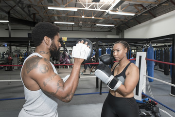 Black woman sparring with trainer in boxing ring