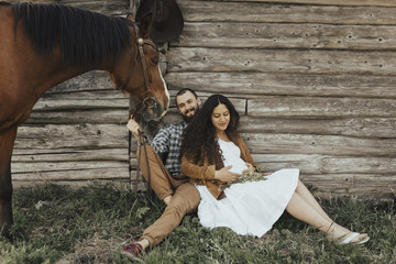 Couple sitting in grass near barn with horse