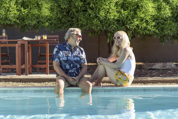 Caucasian couple laughing near swimming pool