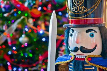 Detail of Soldier Nutcracker with Colorfully Lit and Decorated Christmas Tree Bokeh Background