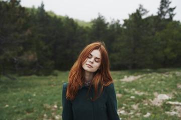 Woman wearing coat in field