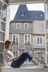 Caucasian woman sitting on windowsill using digital tablet