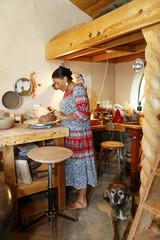 Mixed race woman shaping clay in art studio