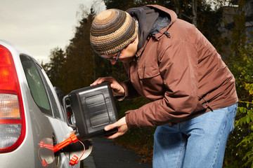 Man with plastic canister filling car tank on street in autumn time